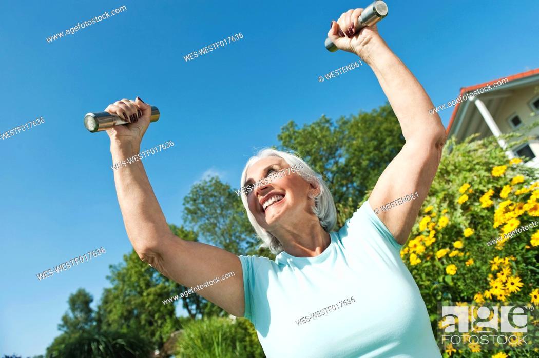 Stock Photo: Germany, Bavaria, Senior woman doing exercise with dumbbell.