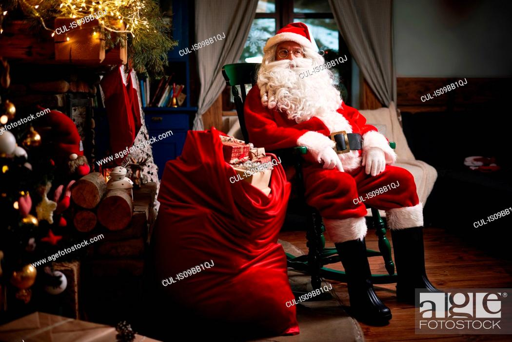 Stock Photo: Portrait of Santa Claus, sitting in chair with sack full of presents.