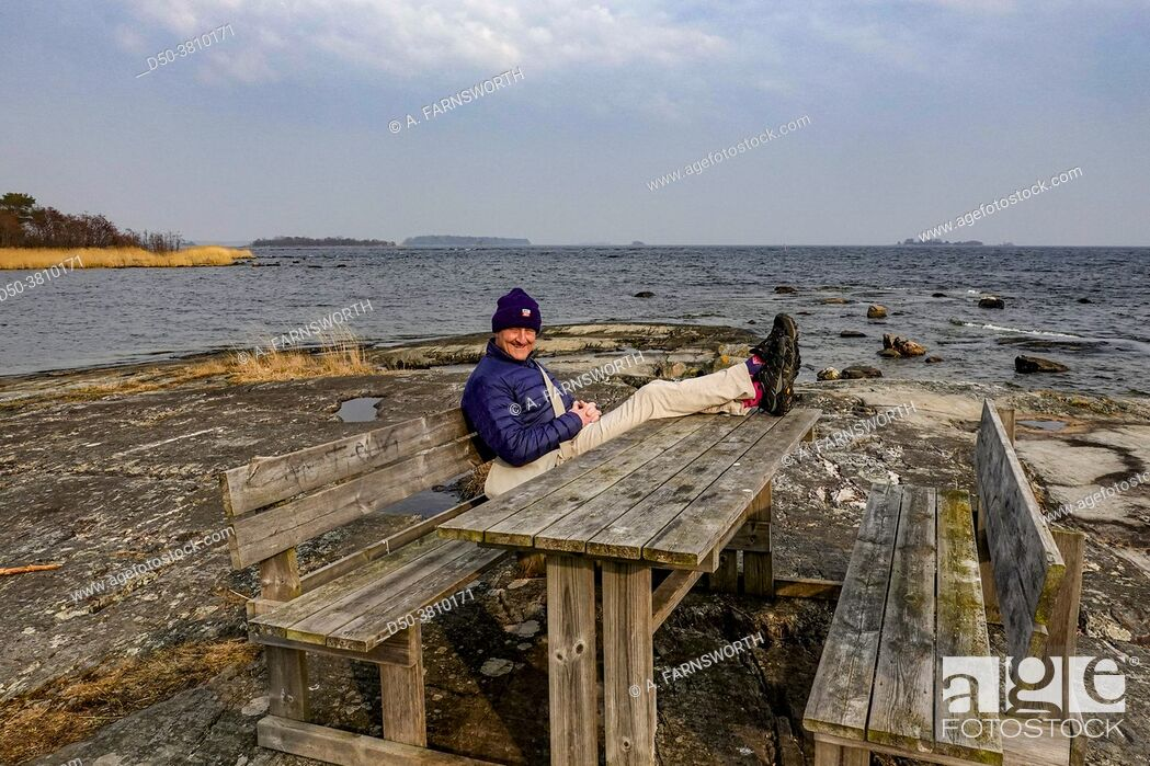 Stock Photo: Ljustero, Sweden A man sits at a picnic table beside the Baltic Sea on an island in the Stockholm archipelago.