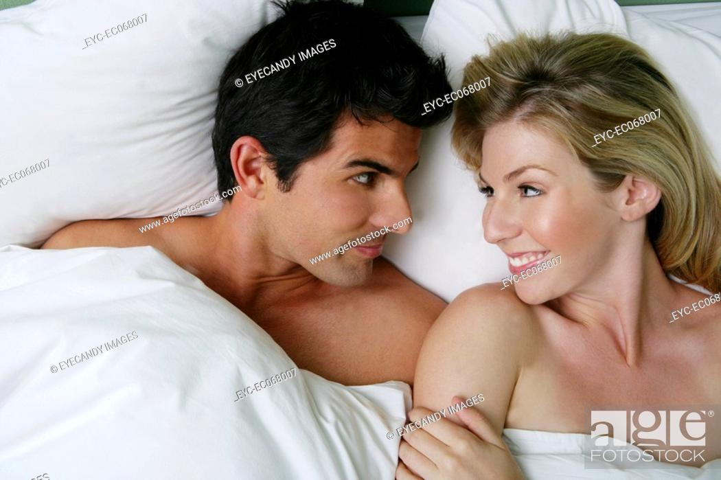Stock Photo: Young happy couple relaxing in bed.