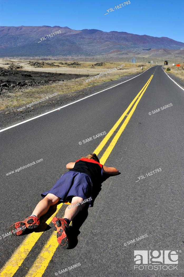 Stock Photo: Woman lying down on the road dividing line, Mauna Kea Volcano, Big Island, Hawaii Islands, USA.