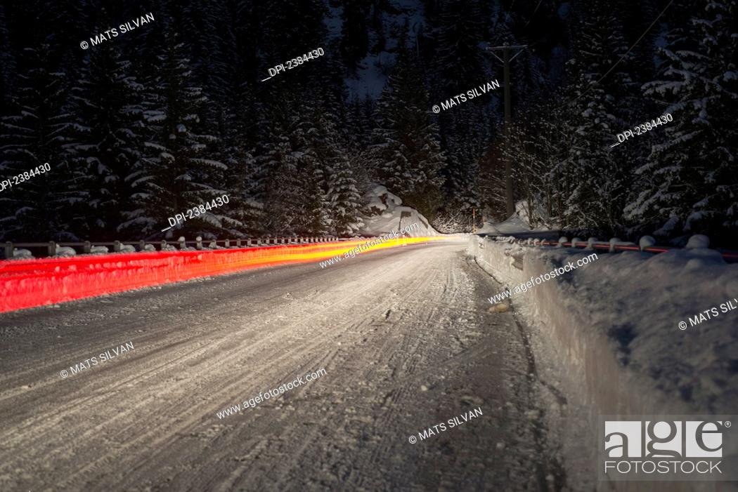 Stock Photo: Light trail from a vehicle taillight on a snowy road at nighttime; Ticino, Switzerland.