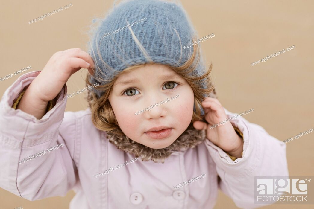 Stock Photo: Portrait of unhappy little girl on the beach in winter.