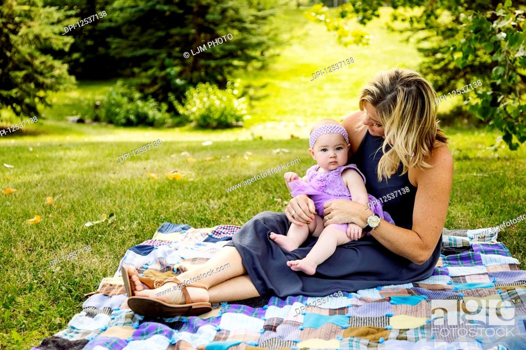 Photo de stock: A mother and her baby daughter sitting on a picnic blanket and spending quality time together while enjoying a family outing in a city park on a warm fall.