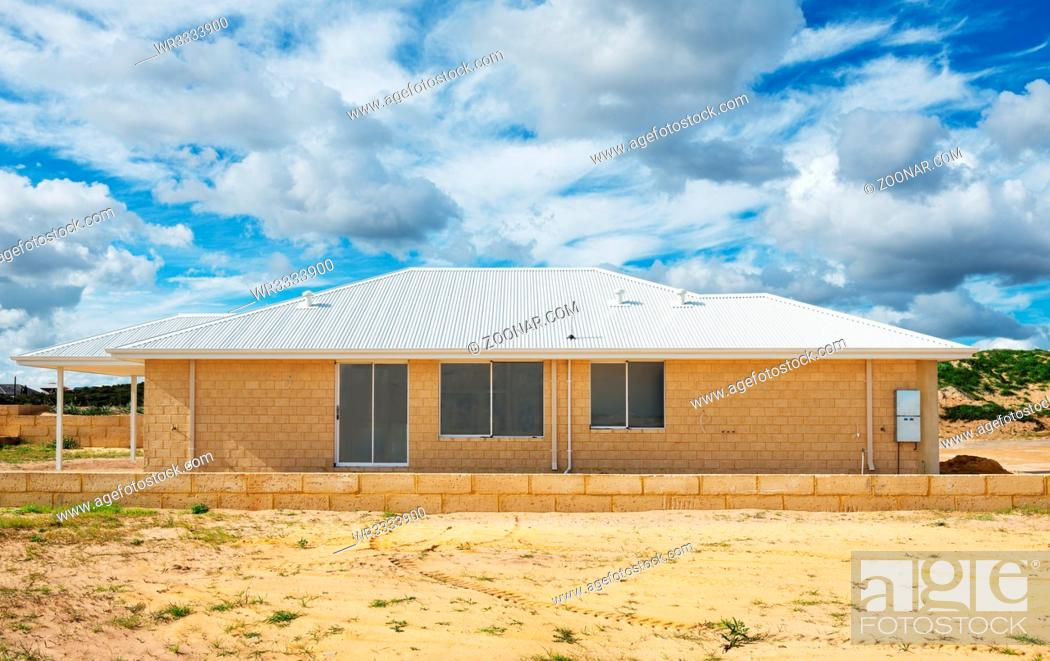 Stock Photo: Side view of new suburban home currently under construction against cloudy sky.