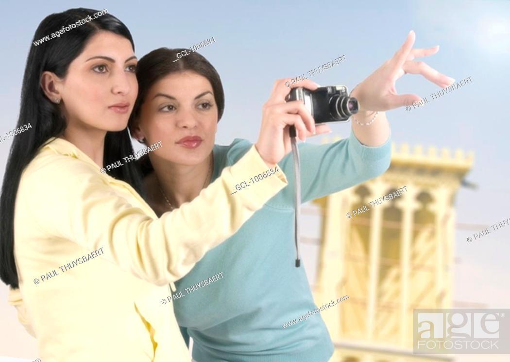 Stock Photo: Two Arab women taking pictures of Dubai landmarks.