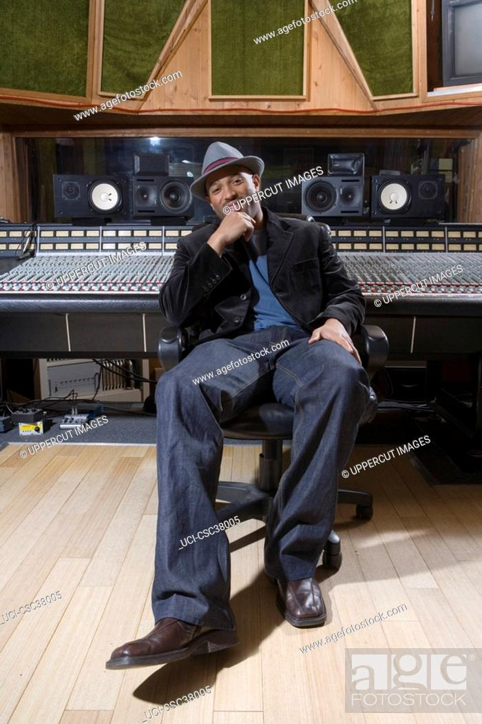 Stock Photo: Music producer smiling in studio.