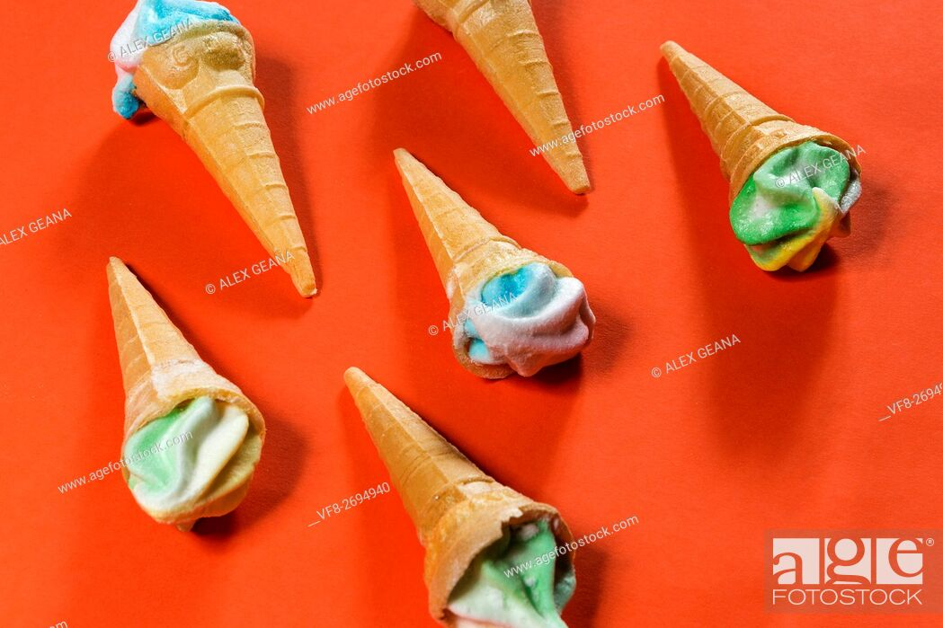 Stock Photo: Sugar candy cones on an orange background, topped with frosted candy.