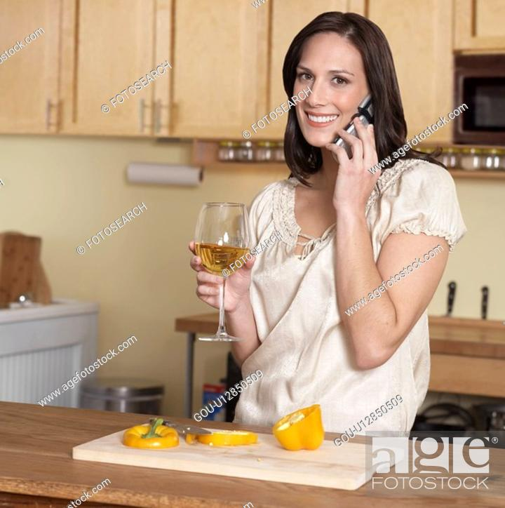 Stock Photo: Mid-Adult Woman on Phone While Cooking.