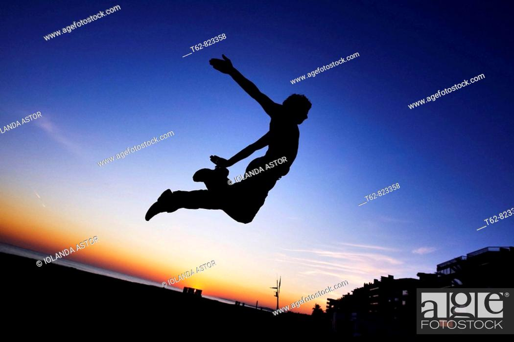 Stock Photo: Parcours: A boy practicing jumps to the dusk in the beach.