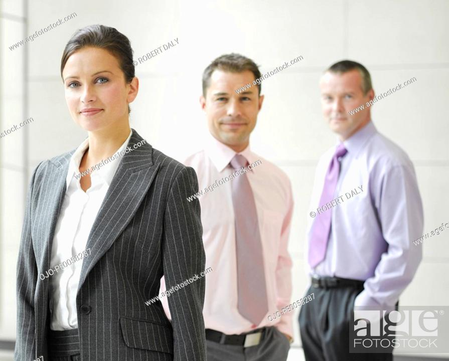 Stock Photo: Three businesspeople in an office.