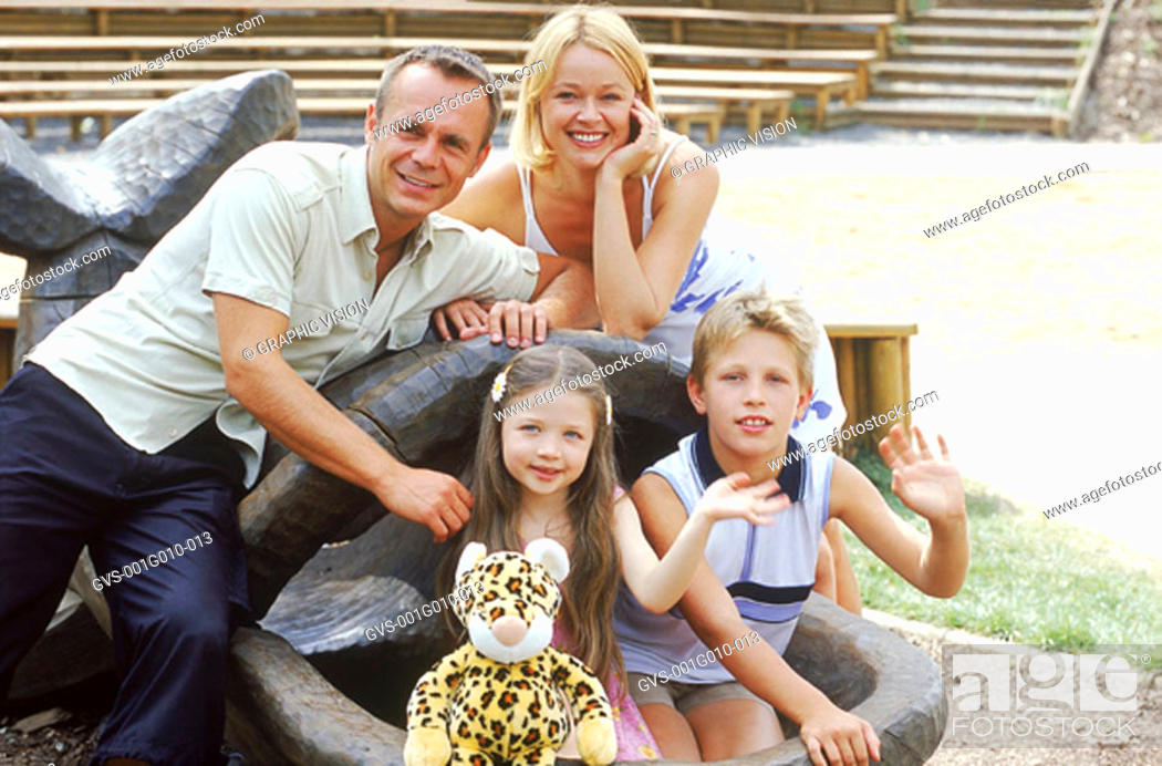 Stock Photo: Portrait of a family sitting on a sculpture smiling.