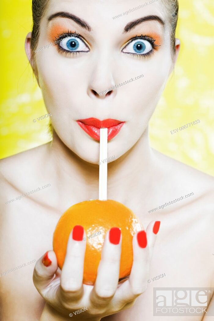 Stock Photo: beautiful caucasian woman portrait amazed drinking with a straw in an orange studio on yellow background.