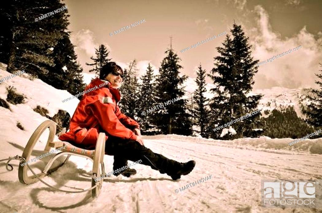 Stock Photo: Mature woman on sledge sunning in winter.