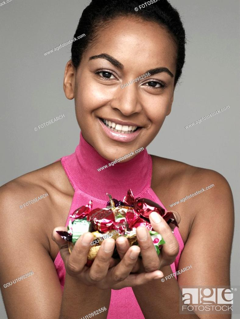 Stock Photo: Young woman holding candies.