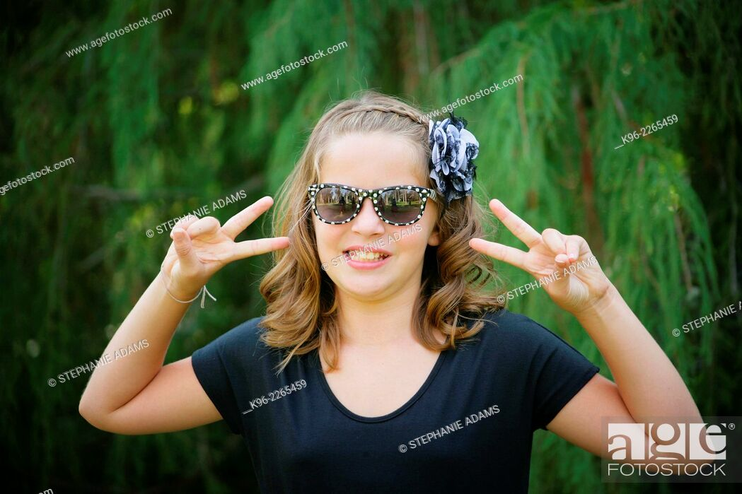 Stock Photo: young girl smiling at the camera wearing sunglasses with peace sign fingers.