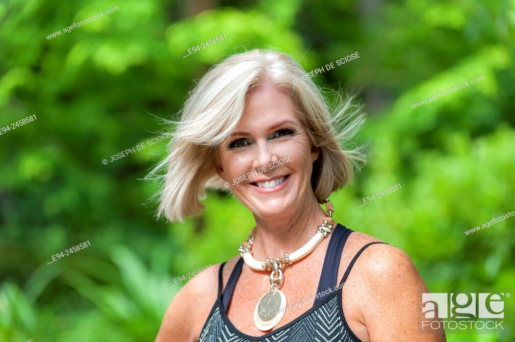 Stock Photo: A portrait of a 56 year old blond woman smiling directly at the camera, outdoors..