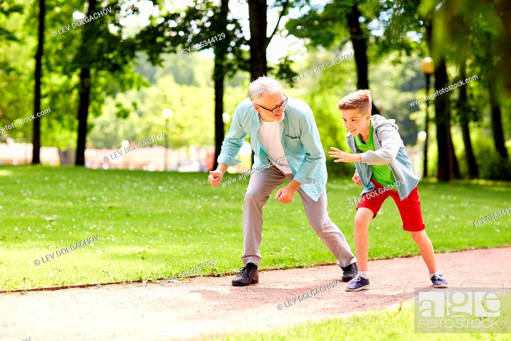 Stock Photo: family, generation and people concept - happy grandfather and grandson racing at summer park.