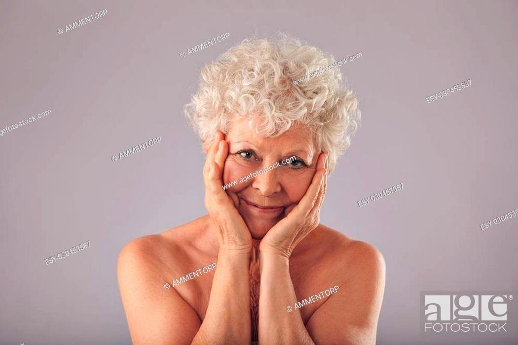 Stock Photo: Portrait of senior caucasian woman touching her face against grey background. Feeling happy for her skin condition at old age.
