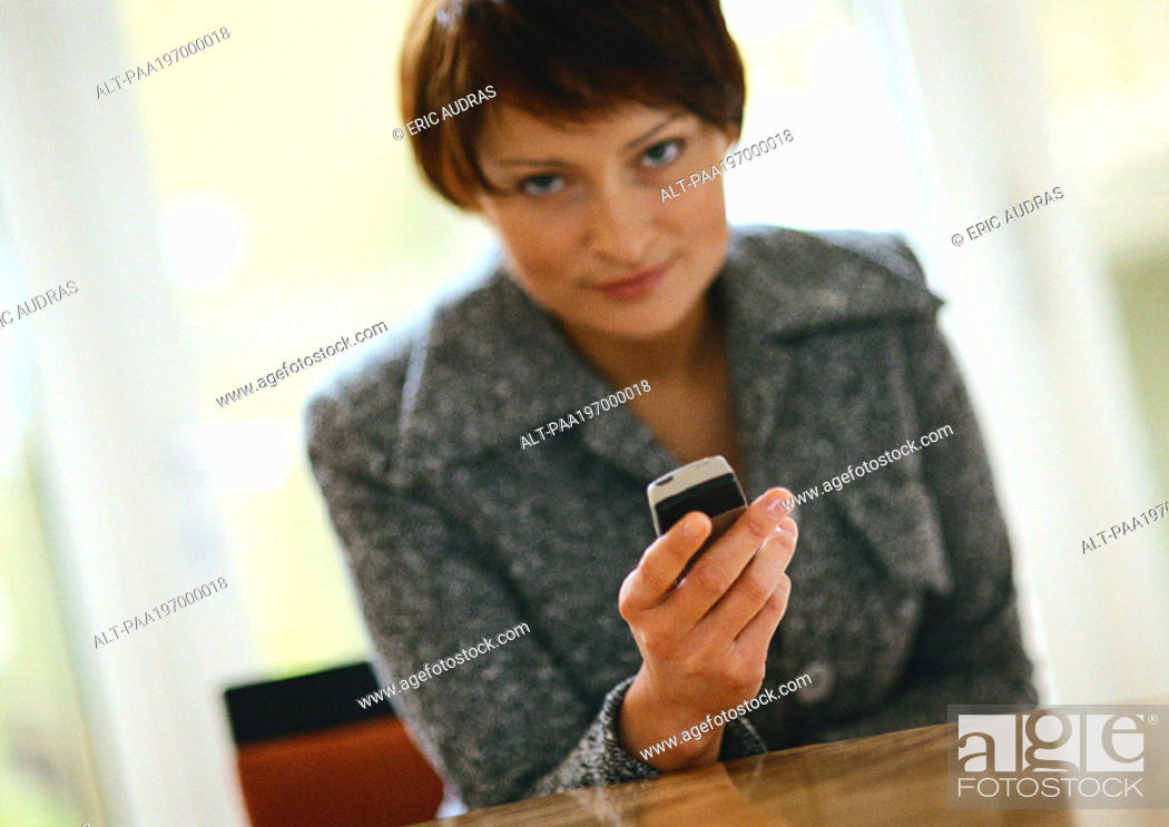 Stock Photo: Businesswoman holding cell phone, looking at camera.