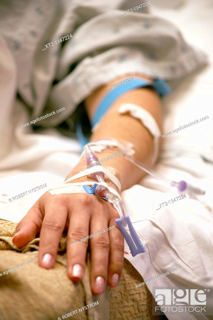 Stock Photo: A womans arm and hand with IV tubes and tape in a hospital bed.