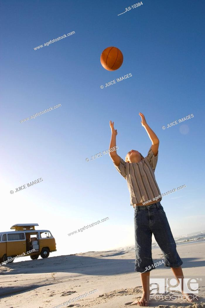 Stock Photo: Boy 6-8 on beach throwing ball up, camper van in background, low angle view.