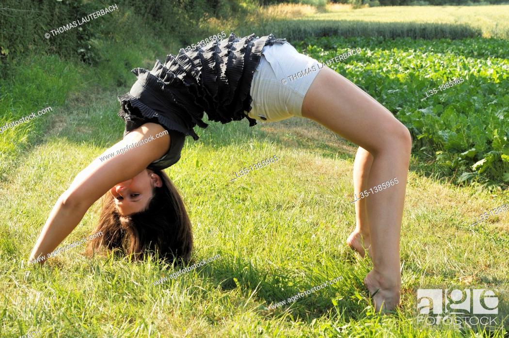 Stock Photo: Young woman doing a cartwheel.