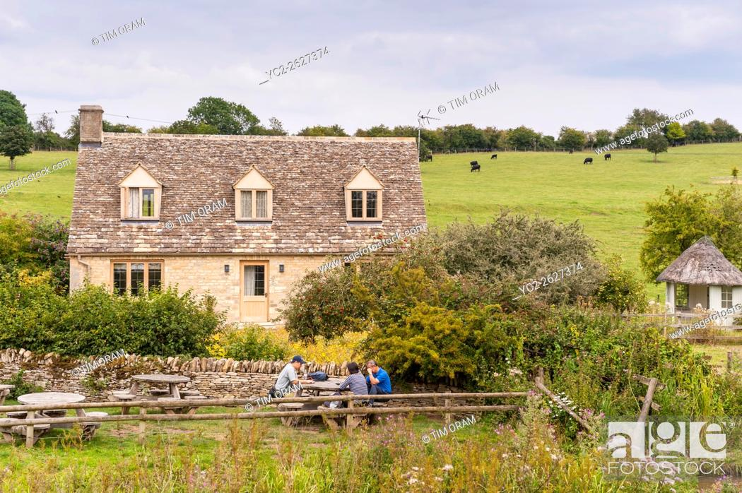 Stock Photo: People in the Beer garden of the Swan Inn at Swinbrook near Burford , Oxfordshire , England , Britain , Uk.