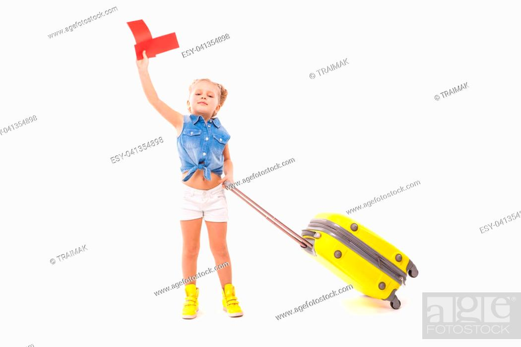 Stock Photo: Isolated on white, cute little caucasian blonde girl in blue shirt, white shorts, sunglasses and yellow boots hold yellow suitcase by the handle, look at camera.