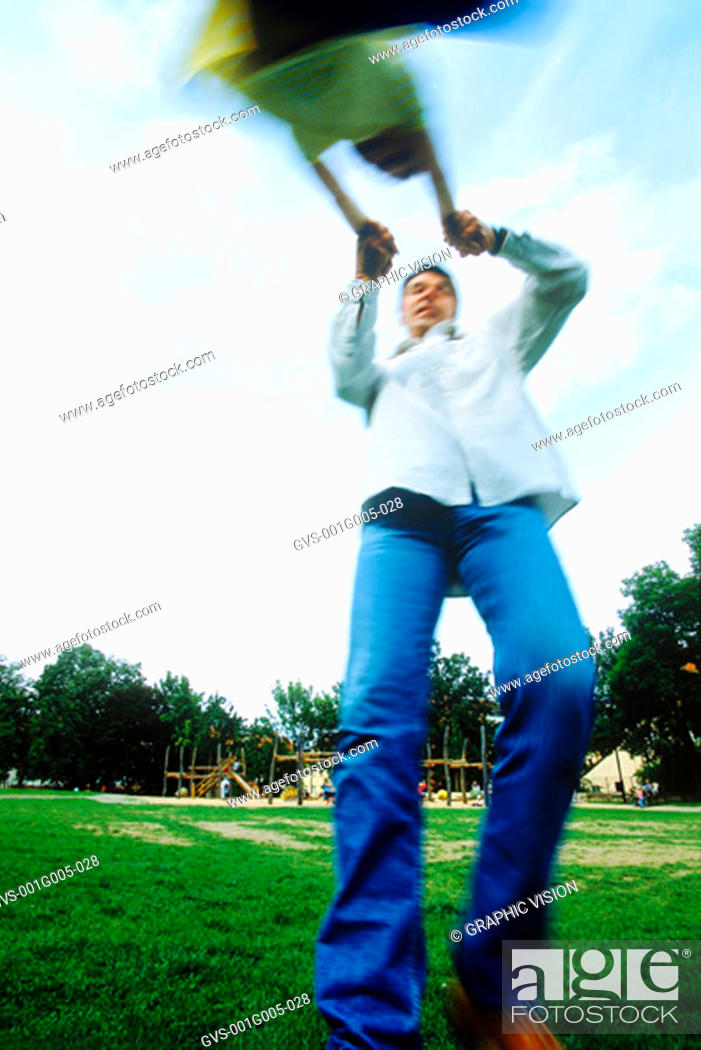 Stock Photo: Blurred low angle view of a man swinging a child by the arms.
