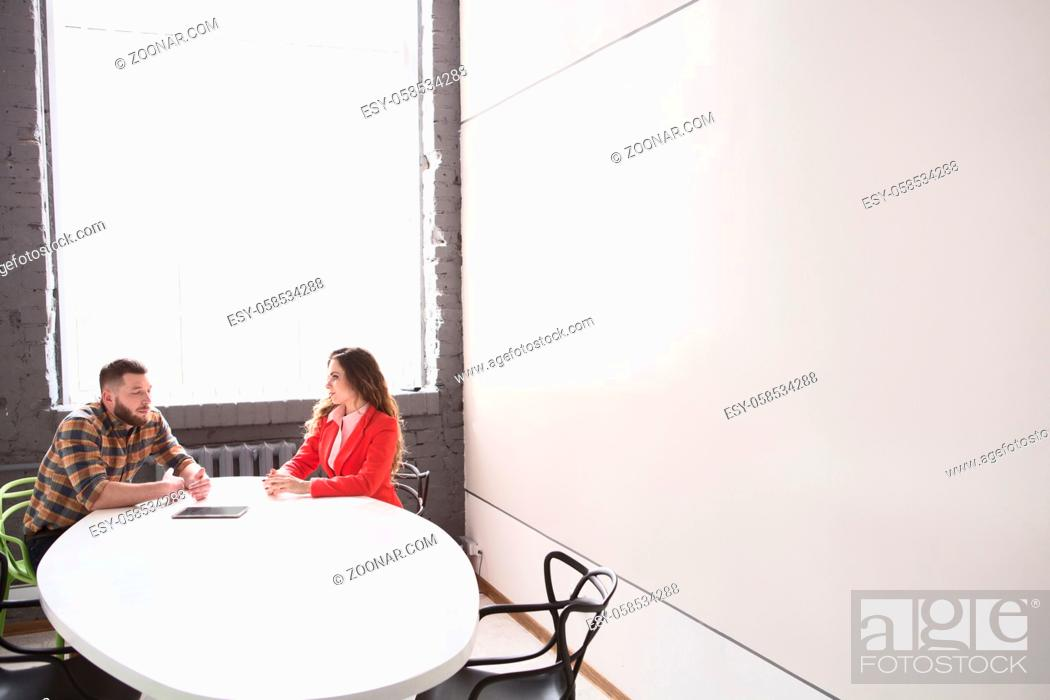 Photo de stock: Picture of business meeting of man and woman in office. Man and woman communicating about business issues in bord room.