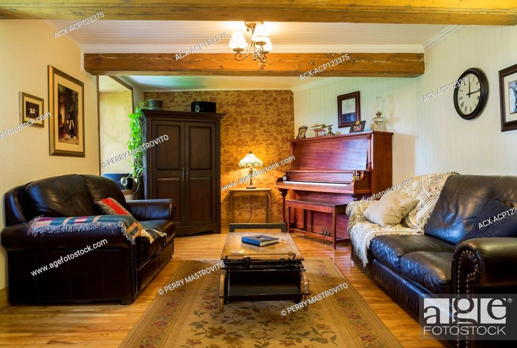 Music room with dark brown leather sofas, upright piano ...