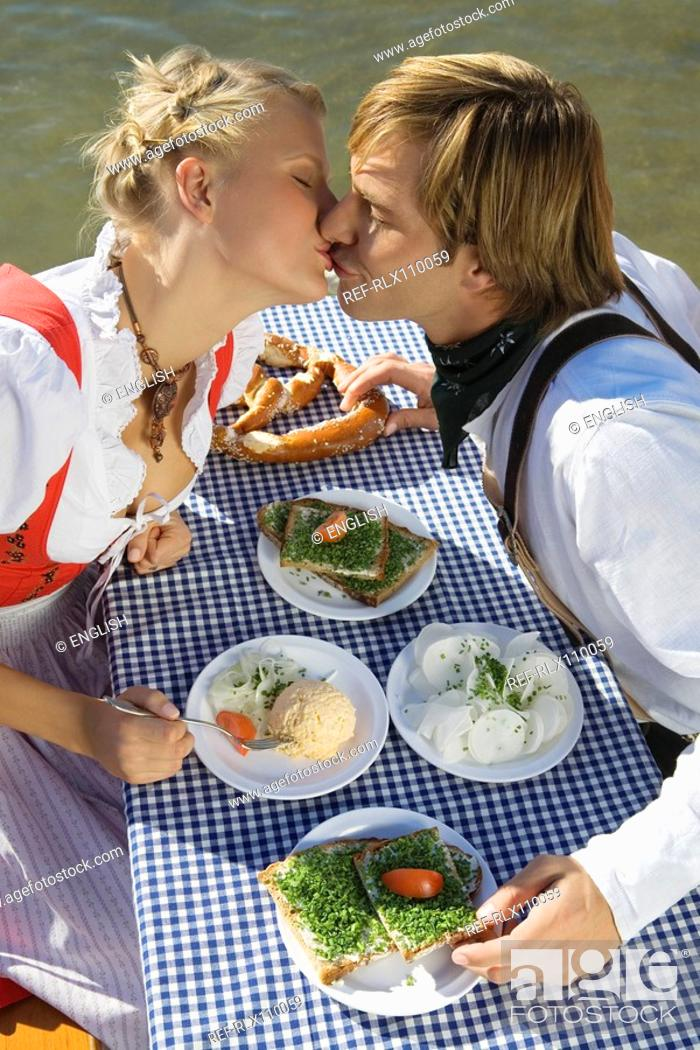 Stock Photo: Young couple in traditional Bavarian outfit, kissing in beer garden, Munich.