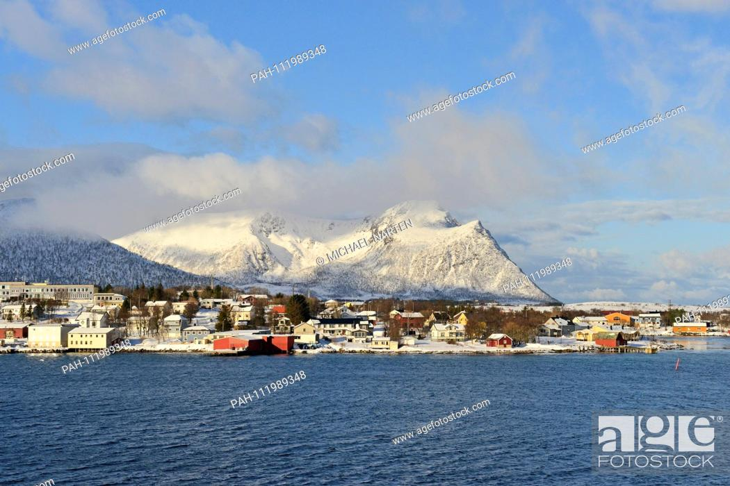 Stock Photo: Several buildings and fishing huts from the small Vesterålen-Village Risøyhamn with the snowcapped mountains from the island Andøya in the background.