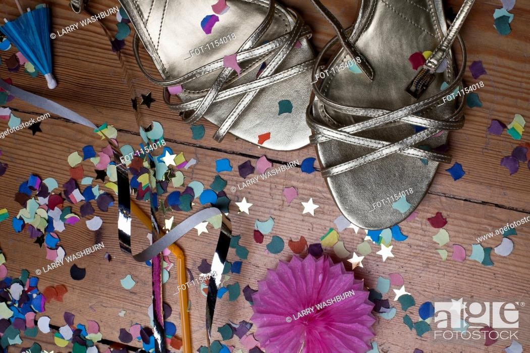 Stock Photo: Metallic strappy heels, confetti and streamers littering a hardwood floor.
