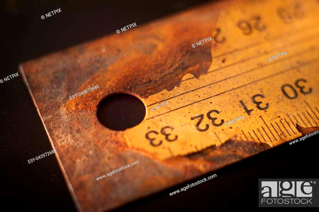 Stock Photo: Old rusty metal ruler with numbered label cracking on black background surface with free copy space.