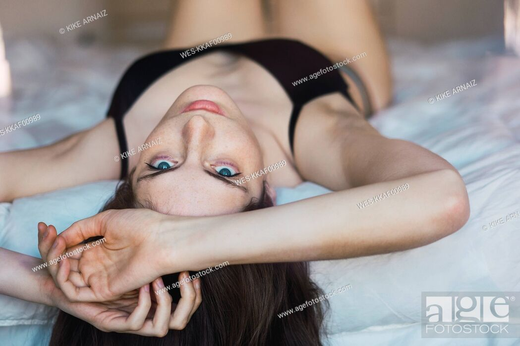 Stock Photo: Young woman in underwear lying on bed.