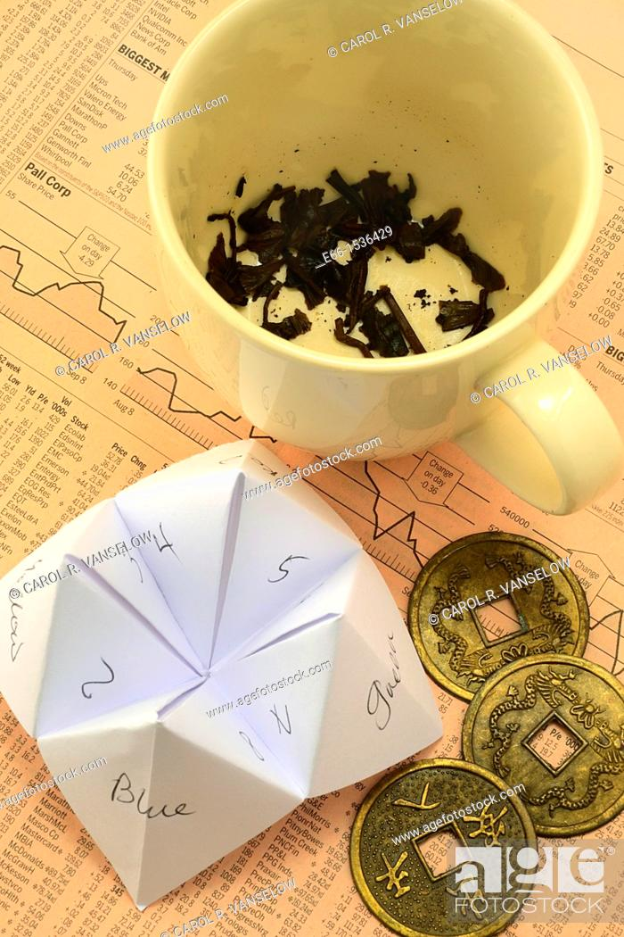 Stock Photo: Where not to go for investment advice: Tea cup with tea leaves, Origami fortune teller - cootie catcher, Coins used with I-Ching laying on European financial.