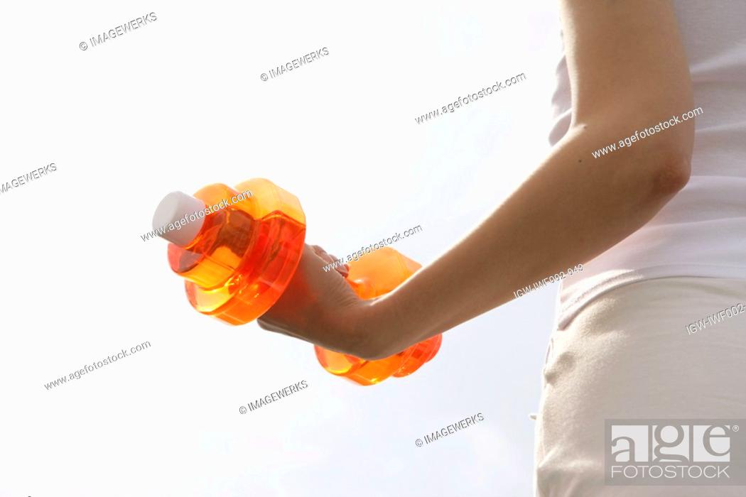 Stock Photo: A woman lifts a dumbbell while exercising.