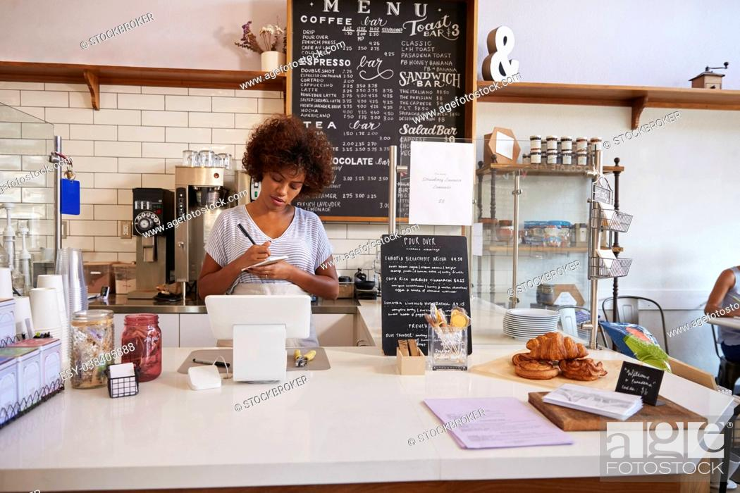Stock Photo: Waitress writing down an order at the counter of coffee shop.