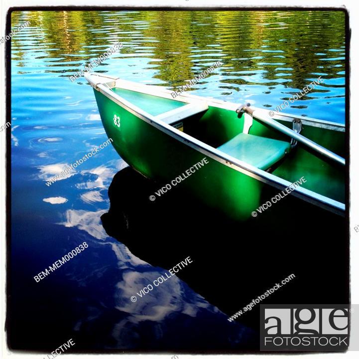 Stock Photo: Green canoe on rural lake.