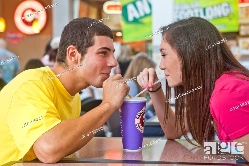 Stock Photo: two teens sharing a beverage.