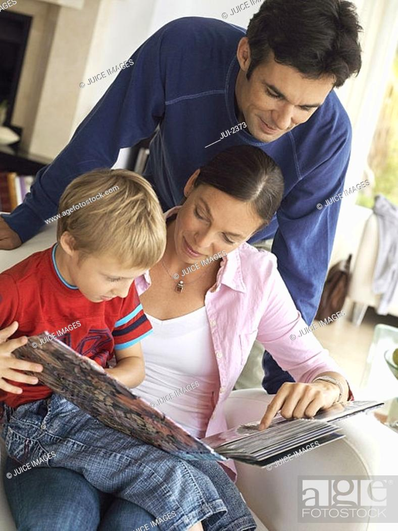 Stock Photo: Family relaxing at home, boy 5-7 in mother's lap in chair, looking at photo album, close-up tilt.