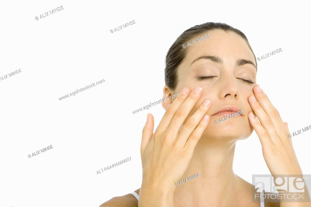 Stock Photo: Woman touching face with both hands, eyes closed.
