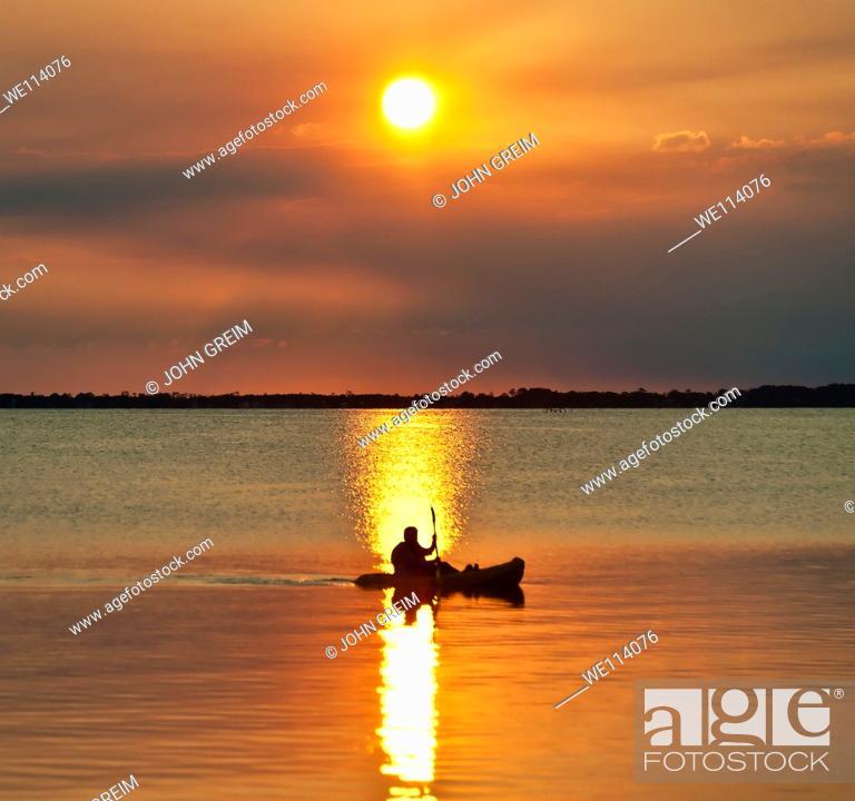 Stock Photo: Man kayaking at sunset.