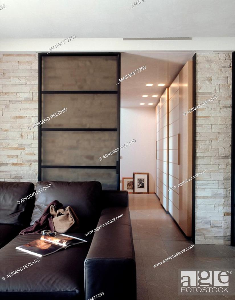 soggiorno con pareti in pietra a vista, porta scorrevole di ...