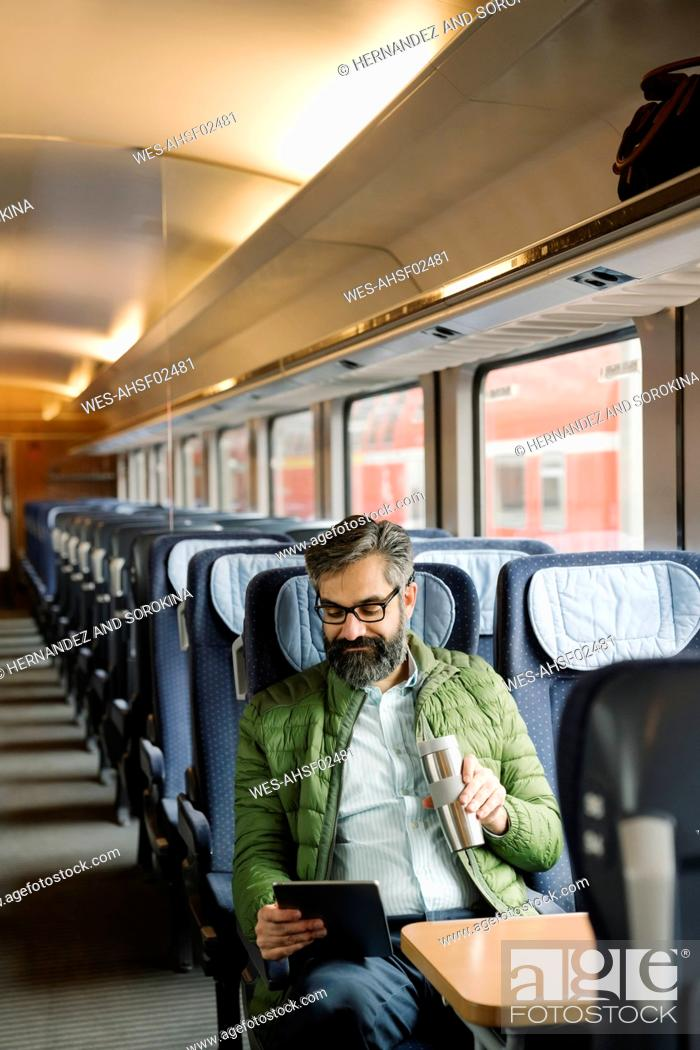 Stock Photo: Man sitting in train using tablet.