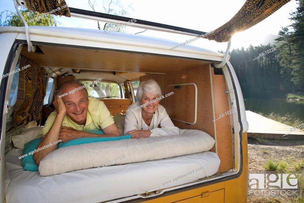 Stock Photo: Senior couple lying in back of camper van, smiling, portrait.