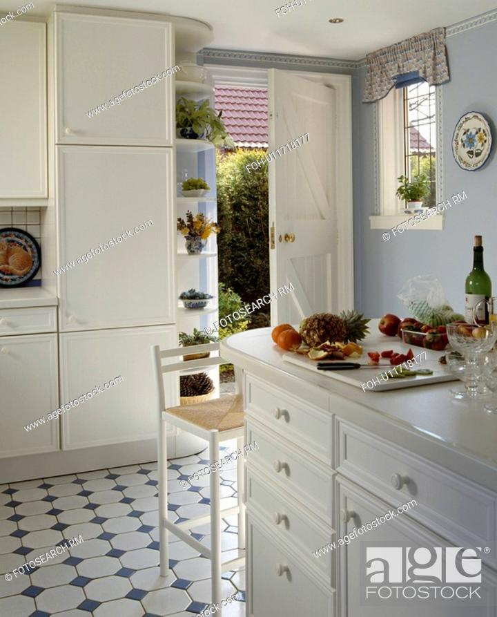 Stock Photo: Blue+white ceramic tiled floor in pastel blue kitchen with white fitted cupboards.