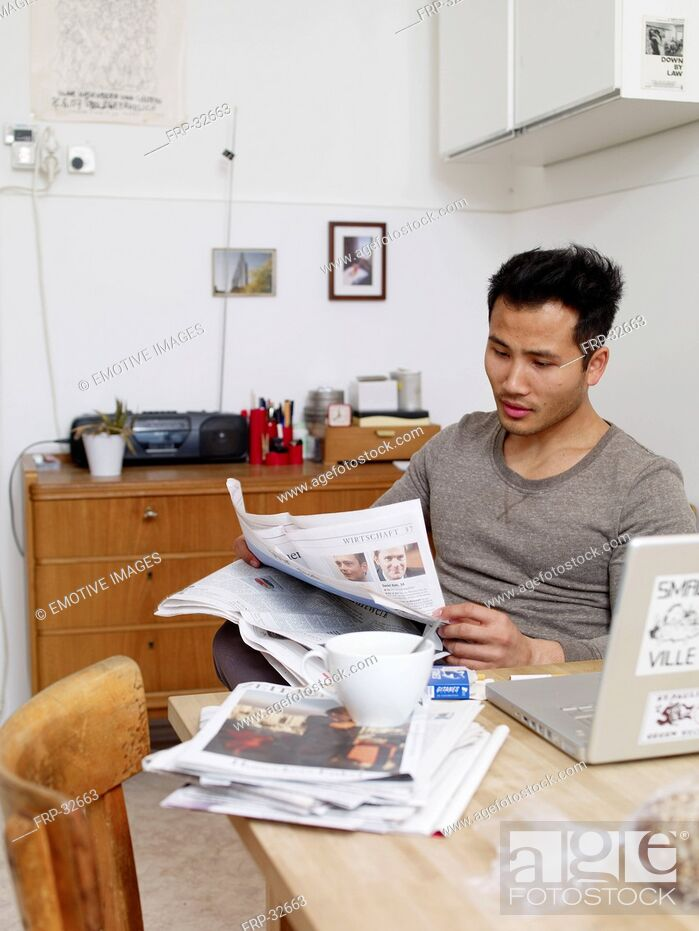 Stock Photo: Man reading newspaper at home.